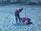 Kate and Maya digging deep to find a clam